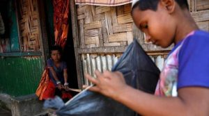 opA Rohingya boy looks on as another boy makes a kite in Leda unregistered Rohingya Refugee Camp in Cox's Bazar